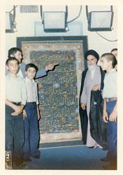 عده ای از نوجوانان با امام  در کنار  نمایش تابلویی از سوره حمد